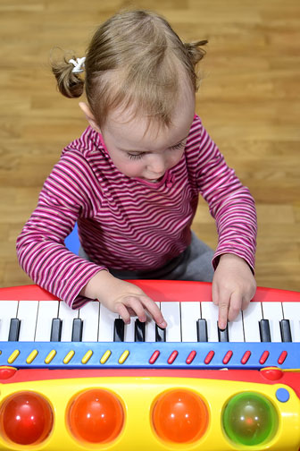 little girl playing a toy piano