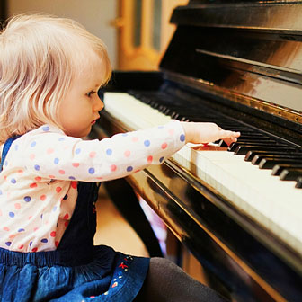 little tow-headed girl playing a big piano